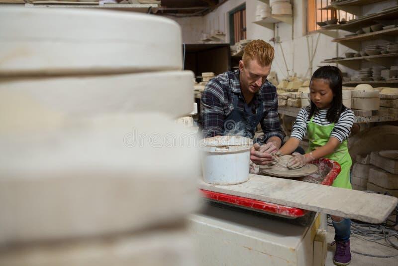 Manlig keramiker som hjälper hans dotter, i framställning av en kruka royaltyfri foto