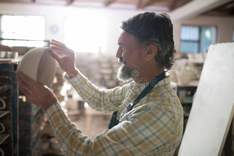 Manlig keramiker som kontrollerar bunken royaltyfri fotografi