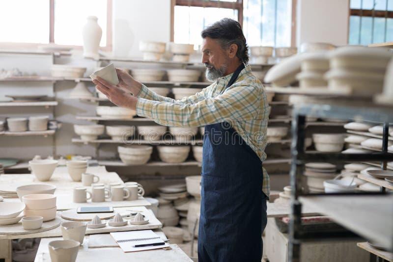 Manlig keramiker som kontrollerar hantverkprodukten arkivfoto
