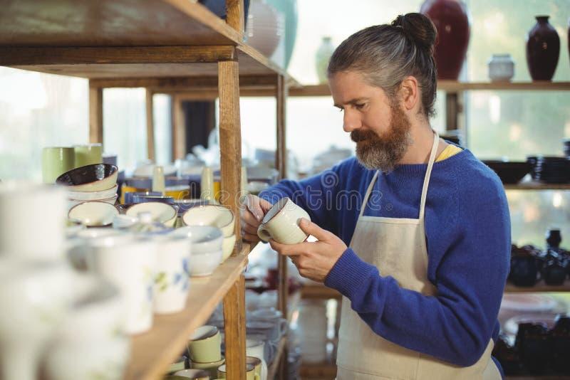 Manlig keramiker som kontrollerar koppen fotografering för bildbyråer