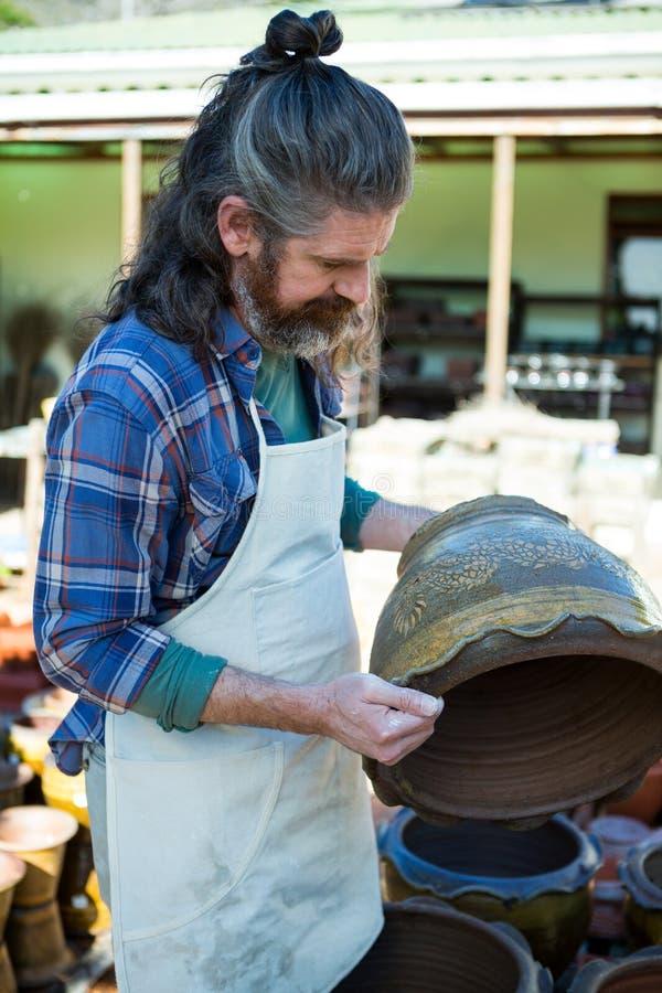 Manlig keramiker som kontrollerar krukan fotografering för bildbyråer