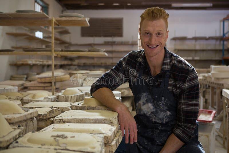 Manlig keramiker som ler i krukmakeriseminarium arkivfoto