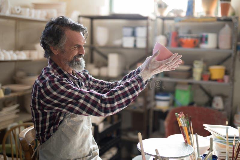 Manlig keramiker som ser den målade bunken royaltyfri bild