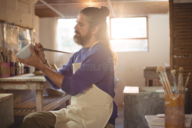 Manlig keramiker som snider på krukan royaltyfri fotografi