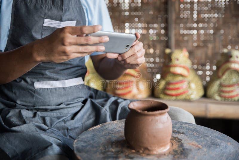 Manlig keramiker som tar bilden av hans produkt i krukmakeriseminarium arkivbild