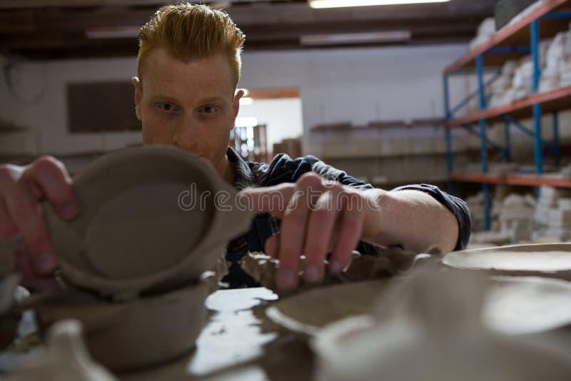 Manlig keramiker som undersöker en bunke arkivfoto
