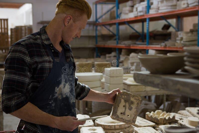 Manlig keramiker som undersöker en lera royaltyfri foto