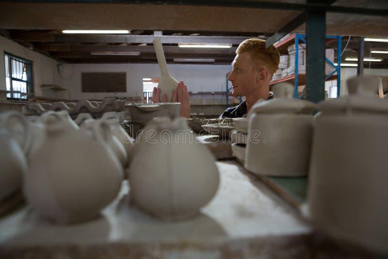 Manlig keramiker som undersöker en lergodsutrustning royaltyfri bild