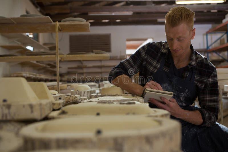 Manlig keramikerhandstil på en dagbok royaltyfria foton