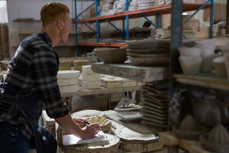 Manlig keramikerhandstil på en skrivplatta royaltyfri foto