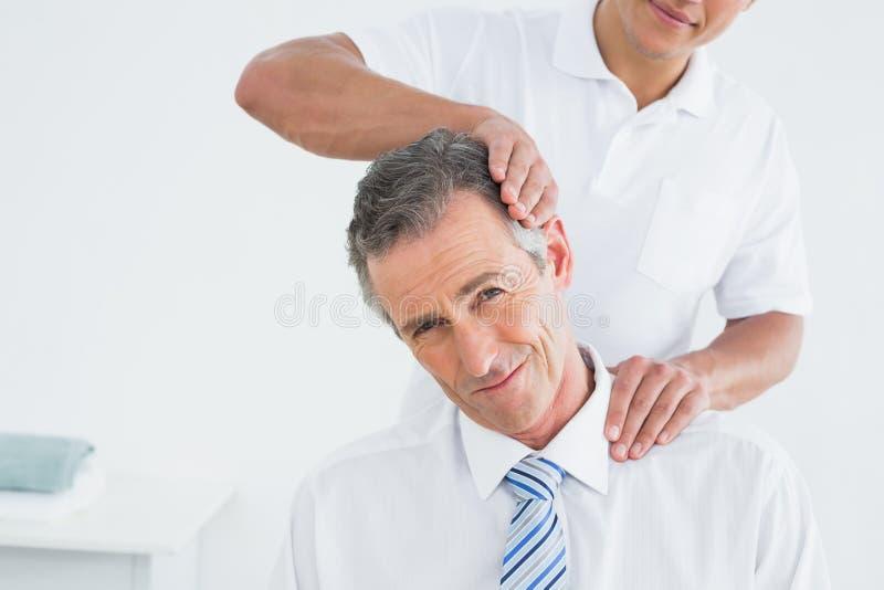 Manlig kiropraktor som gör halsjustering fotografering för bildbyråer