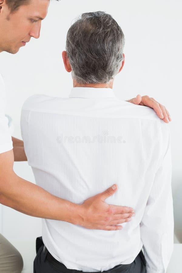 Manlig kiropraktor som undersöker den mogna mannen royaltyfri fotografi