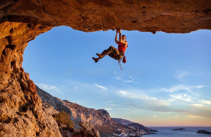 Manlig klättrare som griper på handtag, medan klättra i grotta royaltyfria bilder
