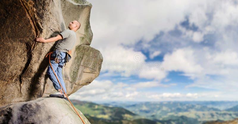 Manlig klättrare som klättrar den stora stenblocket i natur med repet royaltyfri foto