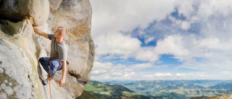 Manlig klättrare som klättrar den stora stenblocket i natur med repet arkivbild