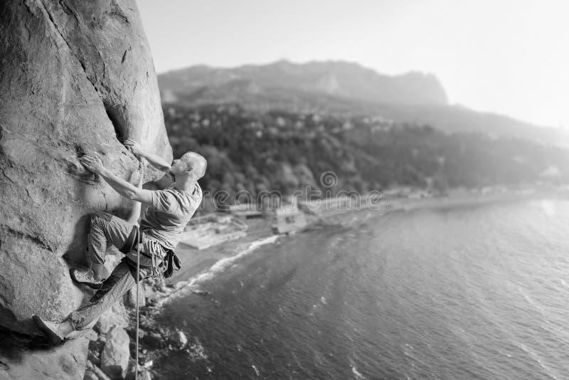 Manlig klättrare som klättrar den stora stenblocket i natur med repet royaltyfria foton