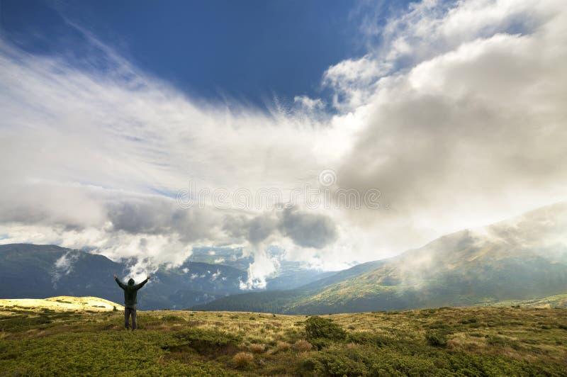Manlig klättrareturist med lyftta armar som står på gräs- kullelutning på gröna berg med vita pösiga moln och kopian för blå himm royaltyfri fotografi