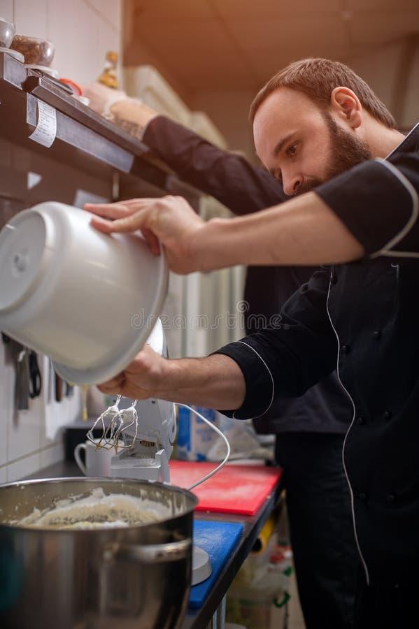 Manlig kock i svart enhetlig matlagningkräm arkivbilder