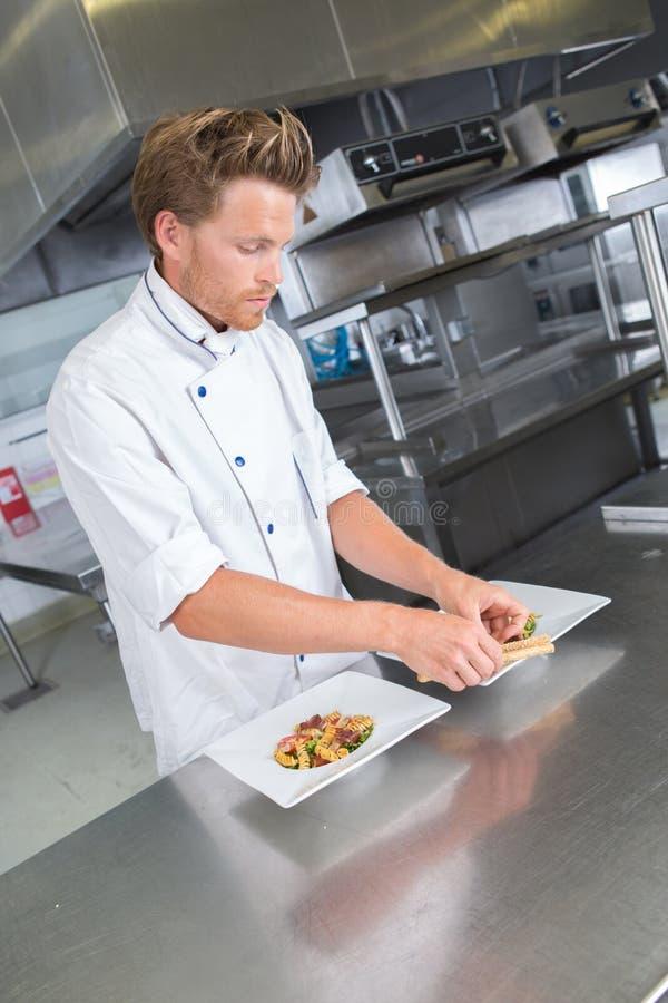 Manlig kock som framlägger mat på plattan royaltyfria bilder