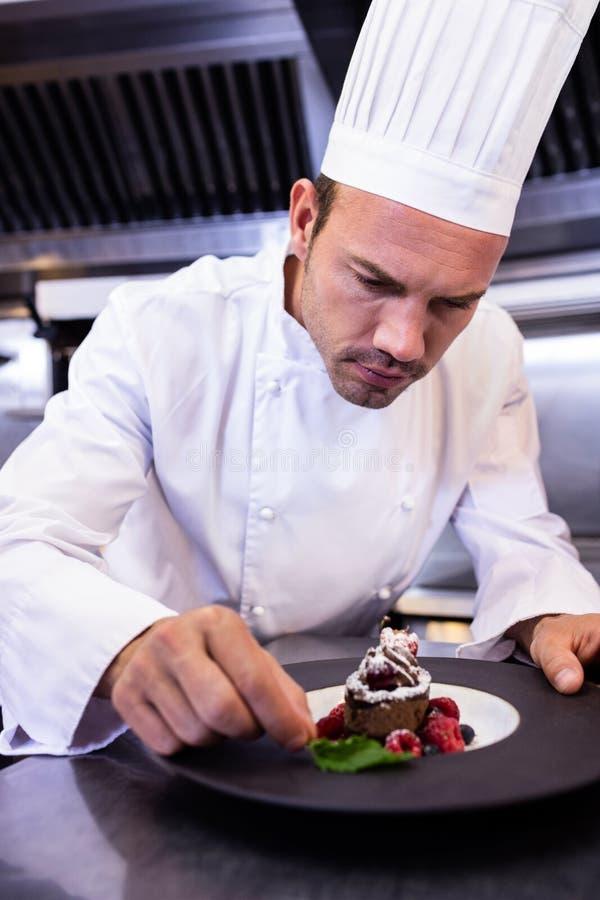 Manlig kock som garnerar efterrättplattan arkivfoton