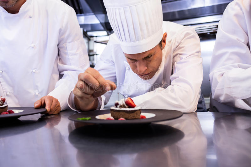 Manlig kock som garnerar efterrättplattan på räknare royaltyfri fotografi