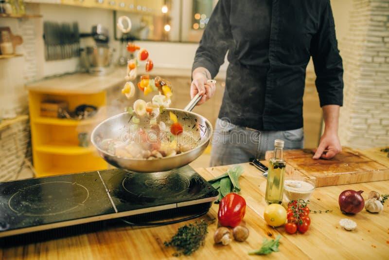 Manlig kock som lagar mat kött med vetables in i pannan arkivfoton