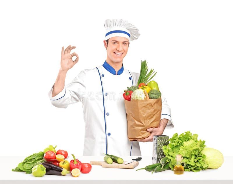 Manlig kock som rymmer en påse full av sund grönsakingridientsne arkivfoton