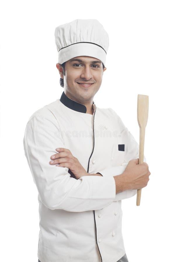 Manlig kock som rymmer en spatel och le arkivbild