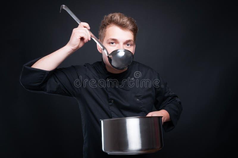 Manlig kock som smakar hans nya soppa från ladel arkivbilder