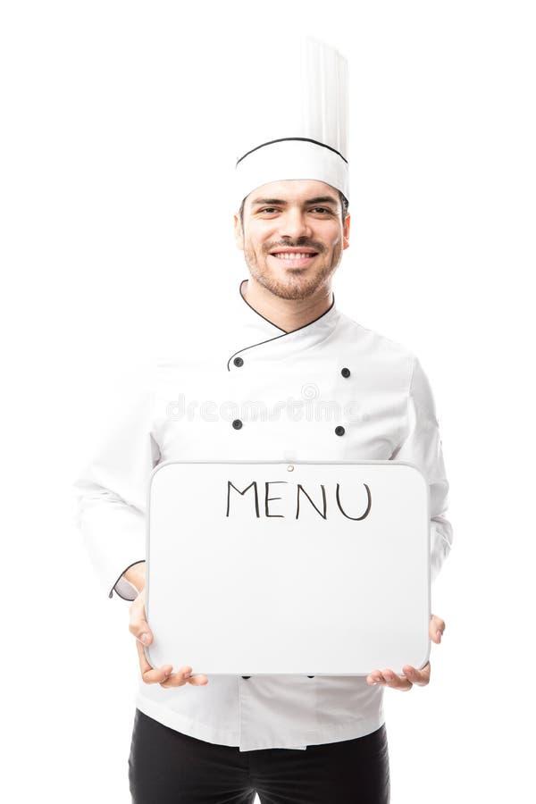 Manlig kock som visar menyn royaltyfri bild