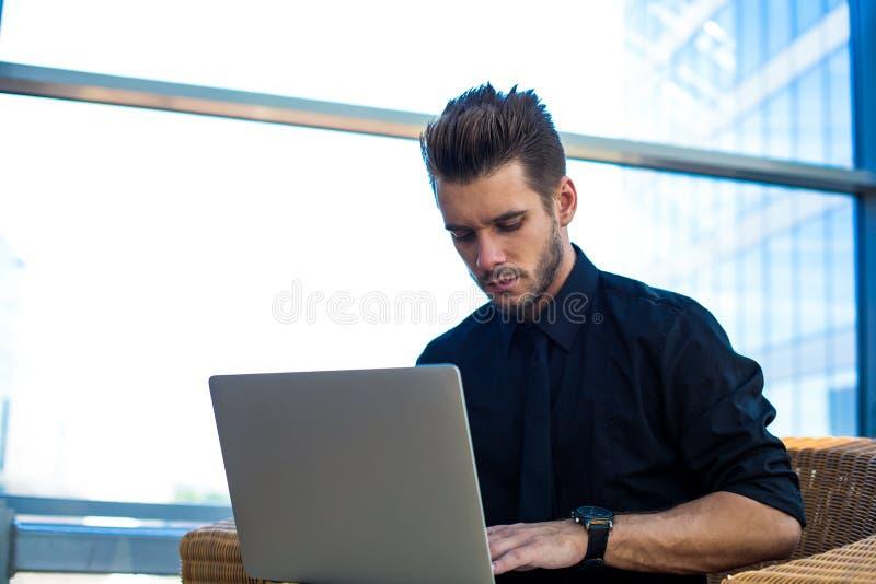 Manlig kompetent ekonom som använder applikationer på netbook arkivfoton