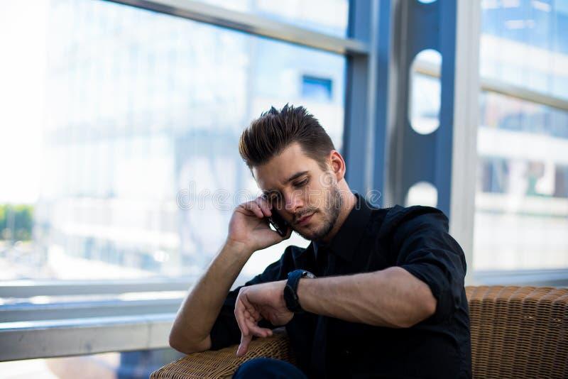 Manlig kompetent mäklare som håller ögonen på på ett armbandsur och i regeringsställning kallar via mobiltelefonen under arbetsda arkivbilder