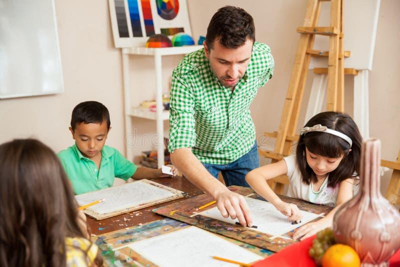 Manlig konstlärare som hjälper hans studenter arkivbild