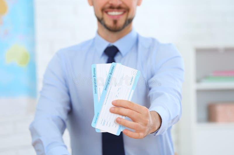 Manlig konsulent som rymmer biljetter i loppbyrå fotografering för bildbyråer