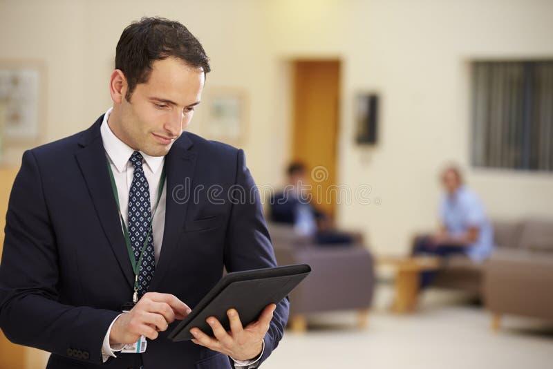Manlig konsulent Using Digital Tablet i sjukhusmottagande fotografering för bildbyråer