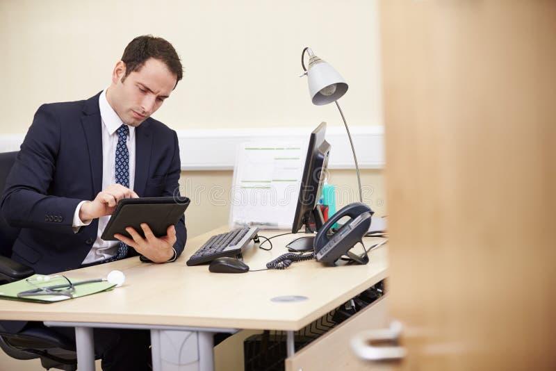 Manlig konsulent Using Digital Tablet på skrivbordet i regeringsställning royaltyfri foto