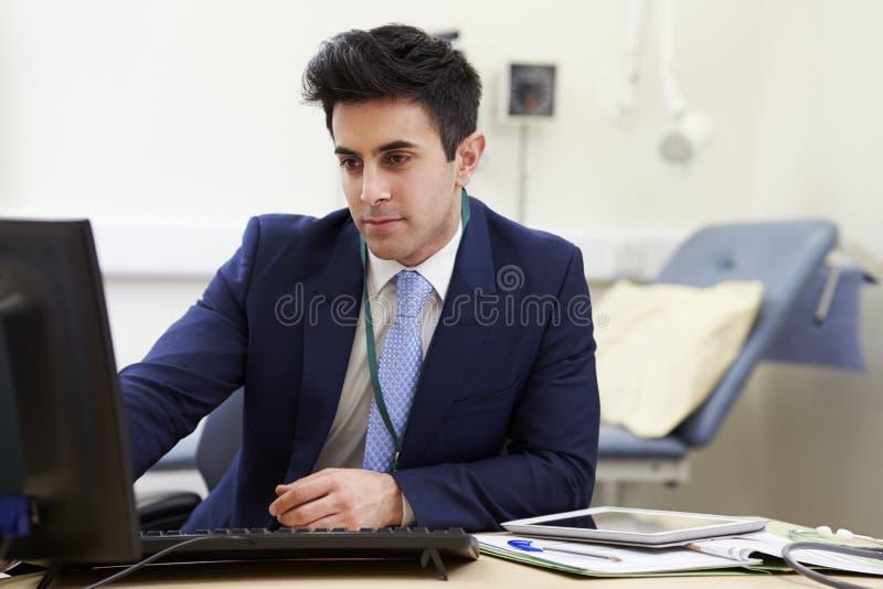 Manlig konsulent Working At Desk i regeringsställning royaltyfri fotografi