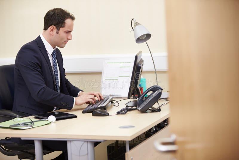 Manlig konsulent Working At Desk i regeringsställning arkivbilder