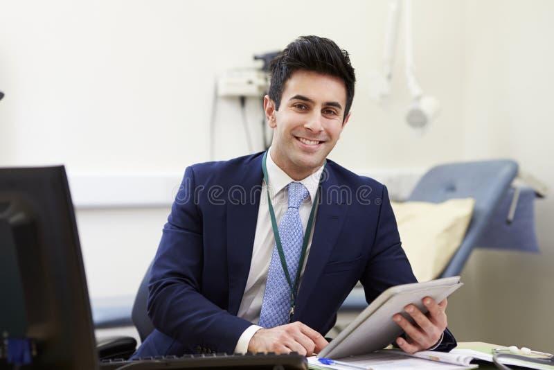 Manlig konsulent Working At Desk som använder den Digital minnestavlan fotografering för bildbyråer
