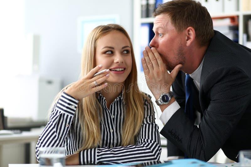 Manlig kontorist som delar någon hemlig kunskap med den kvinnliga kollegan royaltyfri bild