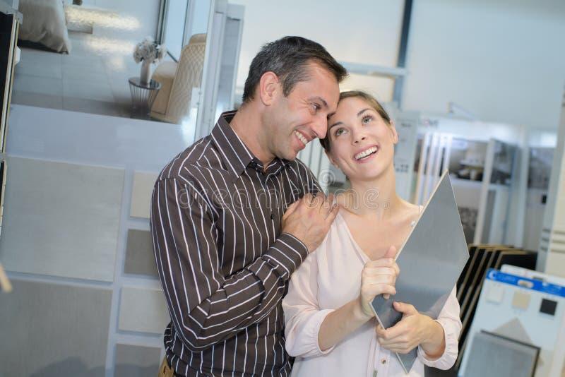 Manlig kontorsanställd som ger kramen till den kvinnliga kollegan royaltyfri foto