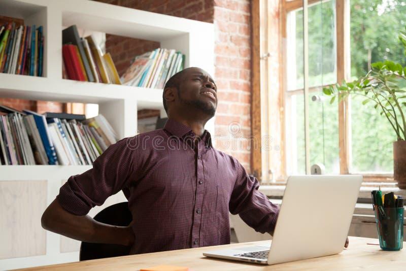 Manlig kontorsarbetare för utmattad afrikansk amerikan som har tillbaka discom royaltyfria foton