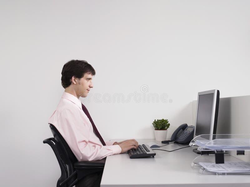Manlig kontorsarbetare som använder datoren på skrivbordet royaltyfri foto