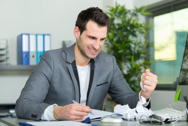 Manlig kontorsarbetare som har svår tid arkivbild