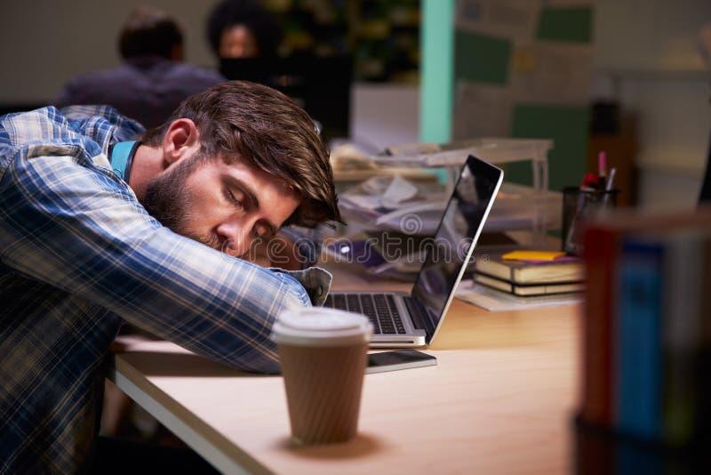 Manlig kontorsarbetare sovande på skrivbordet som sent arbetar på bärbara datorn arkivfoton