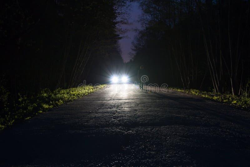 Manlig kontur på kanten av en mörk bergväg till och med skogen i natten Mananseende på vägen mot arkivfoto