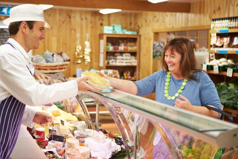 Manlig kund för försäljningsassistentportion i matvaruaffär royaltyfria bilder