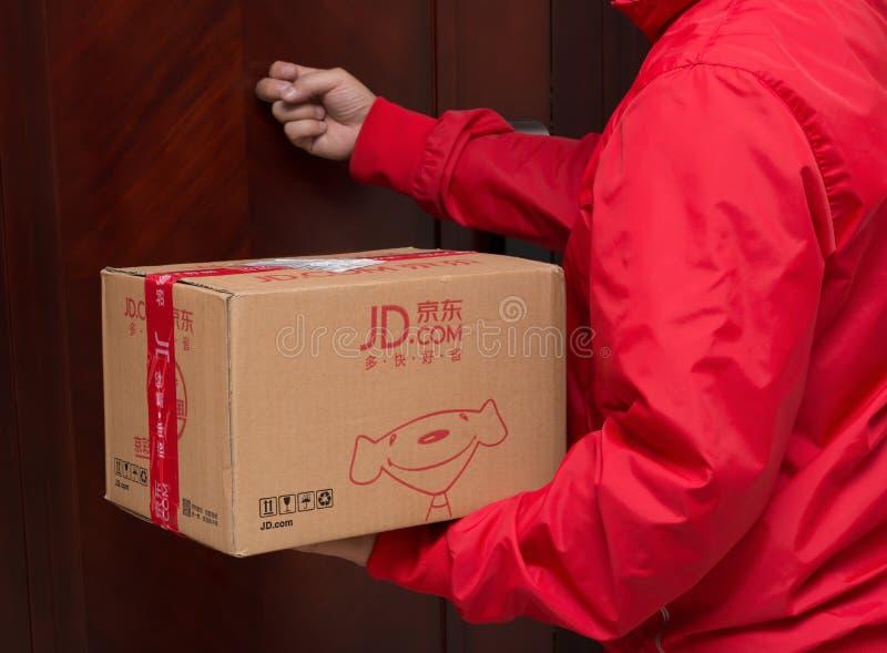 Manlig kurir från JD com som levererar en jordlott för online-shoppingdagar royaltyfria foton
