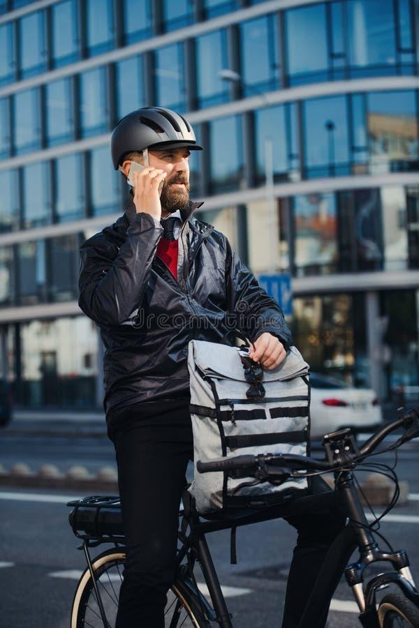 Manlig kurir med cykeln som levererar packar i staden som gör en påringning arkivfoto