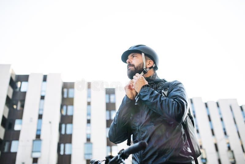 Manlig kurir med cykeln som levererar packar i staden som sätter på en hjälm arkivfoto